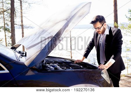 Man fixing his car after it broke on a road