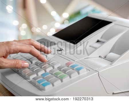 Hand using LCD cash register on blurred bokeh background.