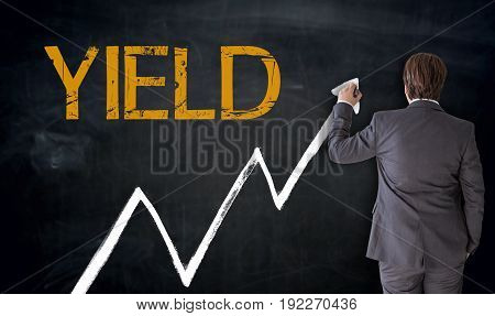 Businessman writes YIELD on blackboard concept picture