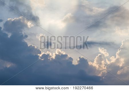 Clouds on blue sky pierced by ray of sunlight horizontal