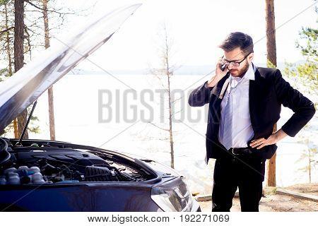 An upset young man calling roadside assistance