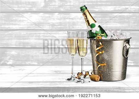 Two champagne flute glasses with bottle of champagne on ice and gold party streamer ribbons on light gray background with copy space.
