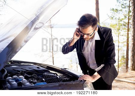 An upset young man calling for a tow truck