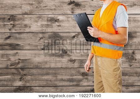 Male worker in orange safety vest holding a clipboard against a wooden background with copy space.