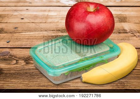 Red apple, sandwich container and a banana for school lunch on a wooden table.