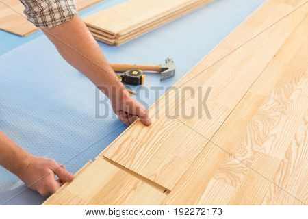 Construction man laying new hardwood floor close up.