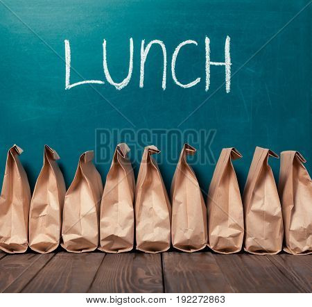 Paper bags on table LUNCH on chalkboard background