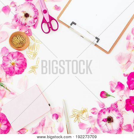 Workspace with pink flowers, petals and clipboard, notebook and accessories on white background. Flat lay, top view.