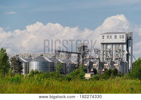 the plant of household chemicals with the metal tanks and pipes surrounded by forest.