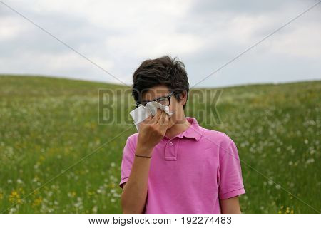 Boy With Allergy And Pink T-shirt Blows His Nose Using A Handker