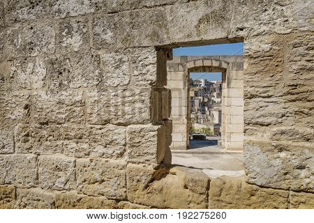 View of ancient stone wall with windows in row in Matera south Italy.