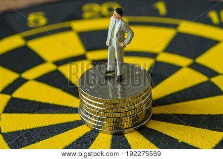 miniature business concept as figure of businessman standing on stack of coins at the center of dartboard.
