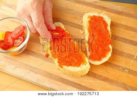A man places cherry tomatoes on bread spread with tapanade with copy space