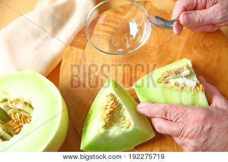 A man is ready to seed pieces of ripe honeydew melon over a wood cutting board