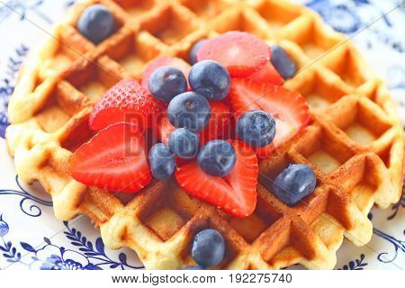 Overhead view of homemade waffle topped with fresh blueberries and strawberries