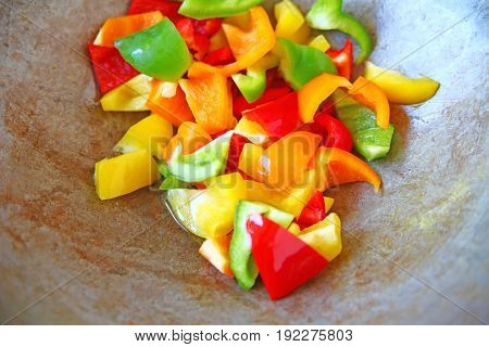 Overhead of wok with red green yellow and orange bell pepper pieces