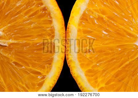 Two slices of orange on a black background macro