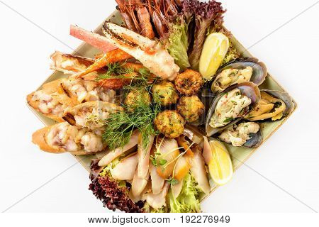 Assorted seafood in a square plate on a white background.