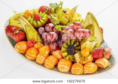 Beautifully decorated fruit platter in a plate on a white background.