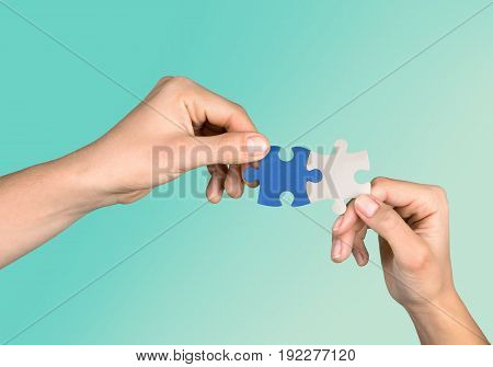 Hands pieces puzzle game green blue background
