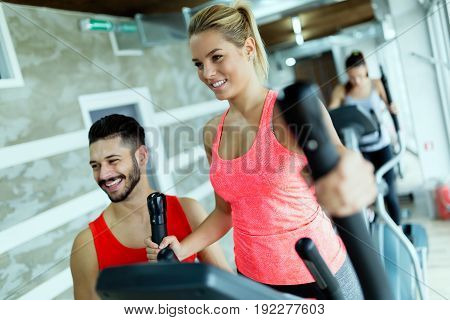Attractive woman working cardio exercises with personal trainer in gym