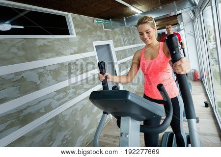 Young beautiful woman doing cardio exercise in gym elliptical trainer