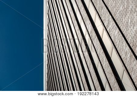 Red brick wall facade with long windows against blue sky. Industrial building from 19th century in Berlin, Germany.