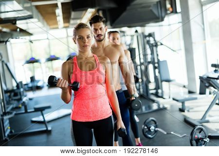 Personal trainer helping young woman with exercises for biceps in gym