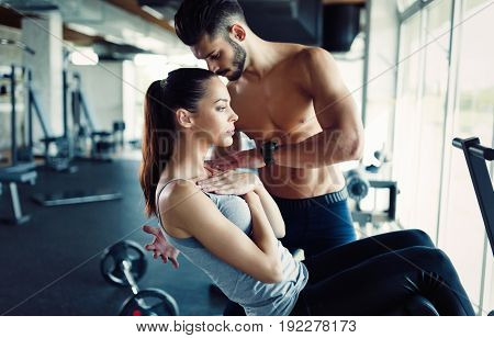 Young woman doing exercises for abs with personal trainer in gym