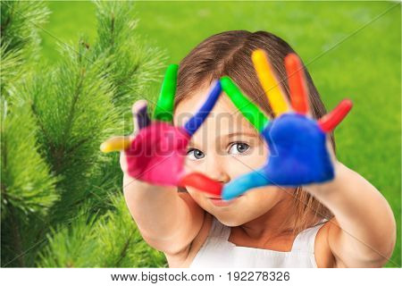 Elementary age girl looking through her colorful painted little hands.