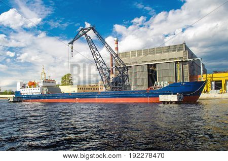 Cargo Ship In The Port And Cargo Crane On The Pier.