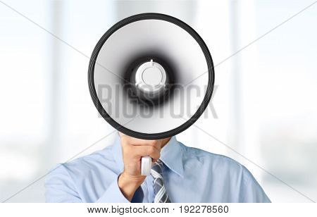 Businessman talking into megaphone that obscures his face.
