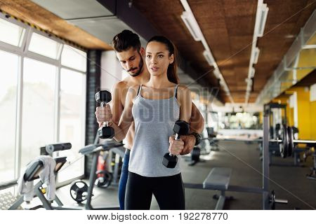 Young sexy woman doing exercises for biceps in gym with trainer