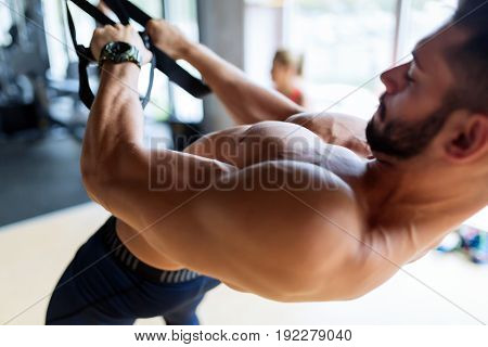 Strong attractive man doing pulling exercises in gym