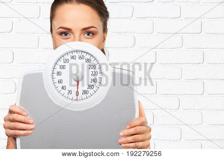 Face of young adult woman partially covered by scale on a white brick wall background with copy space. Diet and weight loss concept.