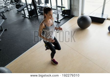 Young beautiful woman doing exercises for legs in gym