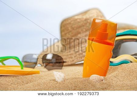 Bottle of sunscreen lotion on straw hat background. Holiday travel concept.