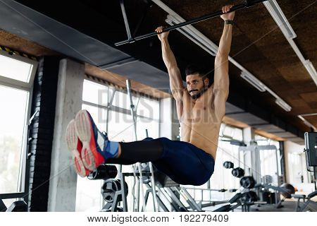 Young strong man performing hanging leg raises exercise