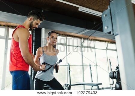 Beautiful woman doing exercises with her trainer in gym pulling