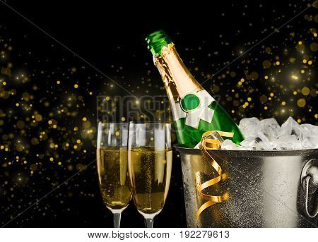 Two champagne flute glasses with bottle of champagne in ice bucket and gold party streamers on black bokeh backgrouns with copy space.