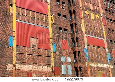 Colorful and artful facade of old abandoned industrial ruin. Windows and doors sealed with metal plates and corrugated metal sheets. Berlin, Germany.