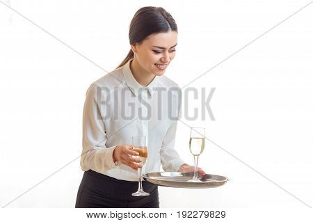 Cheerful young waitress with glasses of wine on a trey smiles isolated on white background