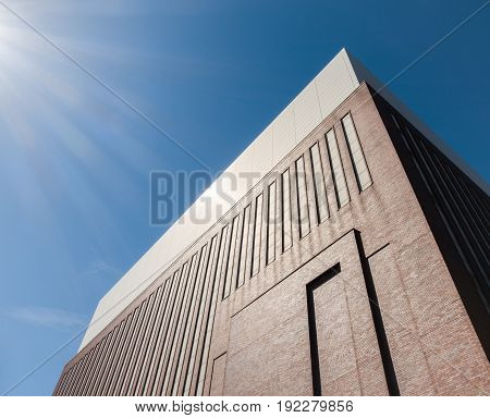 Industrial building with red brick wall facade and long windows against blue sky and sun beams. Power Station from 19th century in Berlin, Germany.