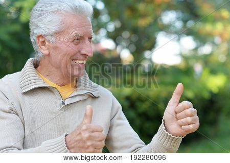 Happy elderly man showing thumbs up   in autumn park