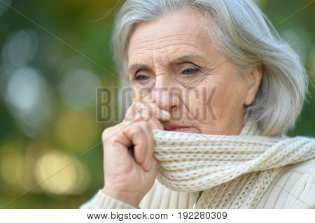Portrait of a senior beautiful sad woman posing outdoors