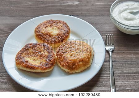 Three Pancakes On White Plate On Dark Table