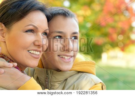 Close up portrait of mother and son hugging outdoors
