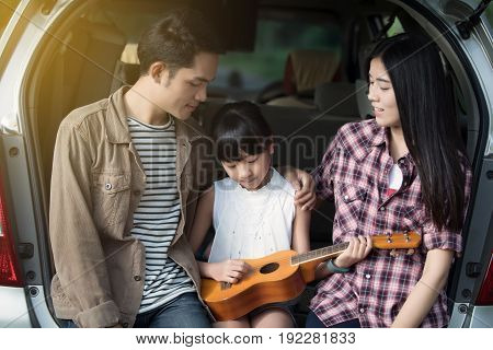 happy little girl playing ukulele with asian family sitting in the car for enjoying road trip and summer vacation