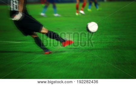 Soft focus and blurry of Soccer player kicking ball in action at stadium