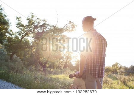 young man with longboard skate watching sunrise